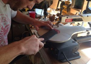 Tom cutting the curved end of his fretboard in Spencer Acoustics Workshop